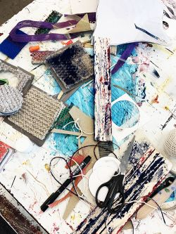 Textile design materials and equipment on table in the textile design studio.