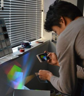 Man interacting with light experiment, holding mobile phone