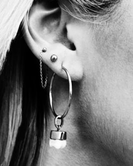 Close up shot of a woman's earring shaped like a tooth