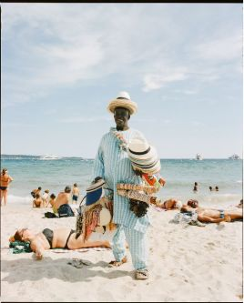 Man on a beach in a straw hat selling gifts. UAL Study Abroad Photography