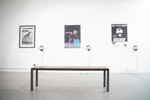 Installation shot of three posters with accompanying headphones