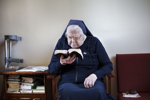 A photograph of an old woman sits in an armchair reading within an interior