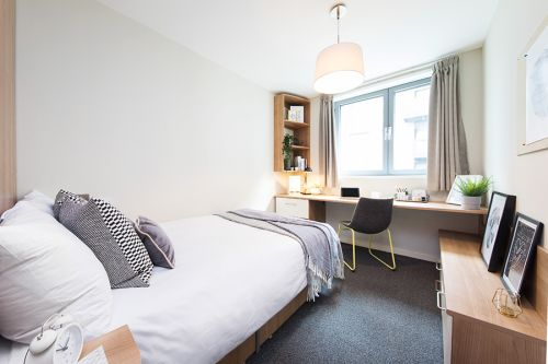 Standard room with 3/4 size bed, bedside table, large wide desk and chair, wide window, shelving unit with additional draw units