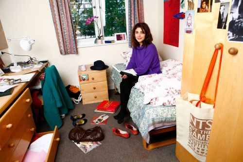 Photo of a female student sitting on a bed in a room at Cordwainers Court