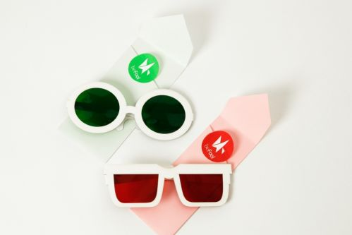 Two pairs of white-rimmed sunglasses. One square-rimmed, the other rounded.