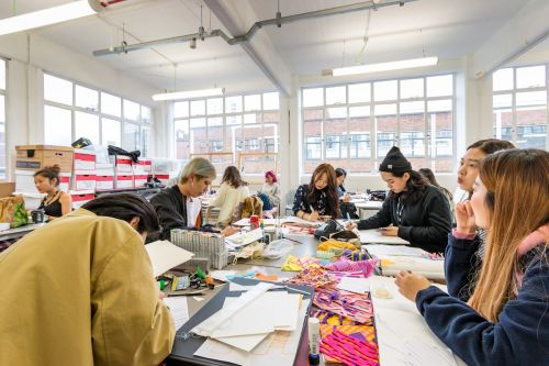 Students working at a desk inside Central Saint Martins' Archway campus
