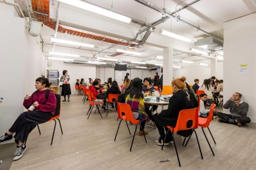 Students at a desk eating lunch at Central Saint Martins' Archway campus
