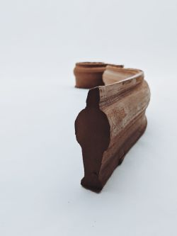 Extruded figure of man in brown clay