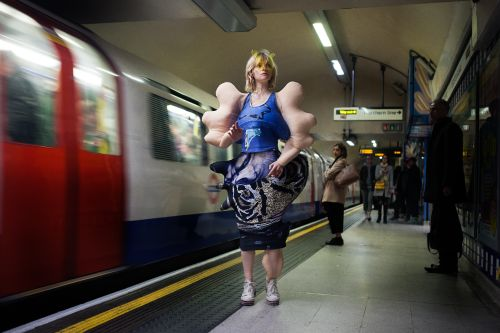 model at undergound station beside a moving tube, wearing a bodysuit garment with disfigured limbs