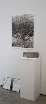 a print mounted on a wall behind a stone on a plinth