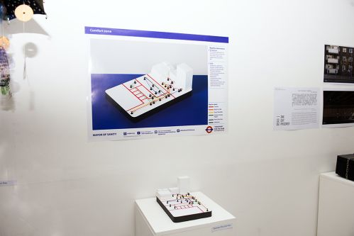 A map-like sculptural object sits on a plinth underneath a poster featuring a rendering of the same object.