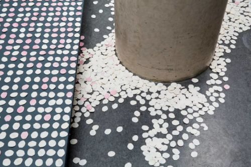 Cut out rose petals arranged around a concrete cylinder