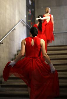 Three women wearing red dresses walking up a set of stairs