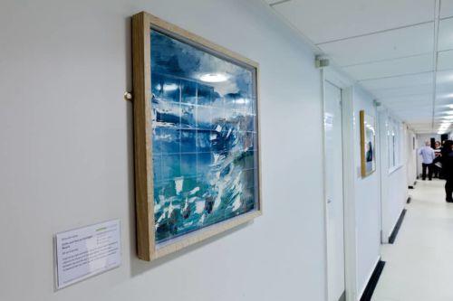 A blue coloured framed artwork on a wall
