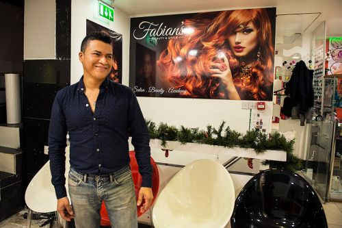 Fabian, owner of Fabian Beauty Stylist hairdressing salon in Elephant Road, and his new logo, designed by Caley Dewhurst, in the background.