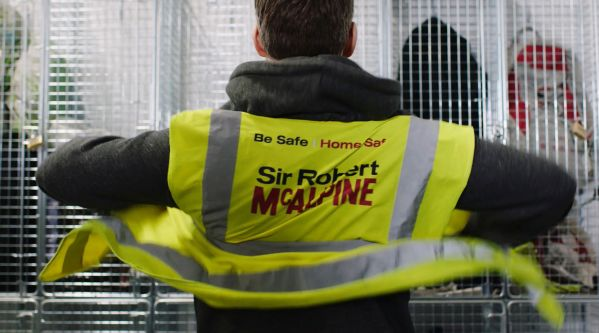 Still from a Health and Safety film showing a man facing a white locker, displayer the back of his Sir Robert McAlpine high-vis jacket.