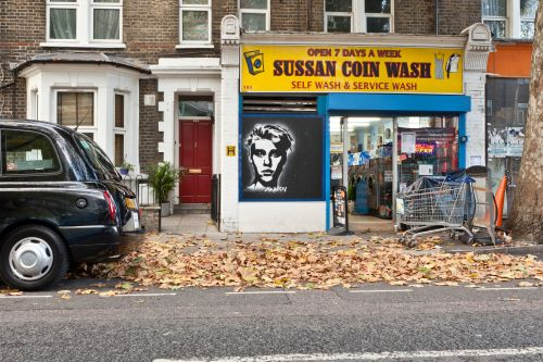 The front of a laundrette on an autumn street