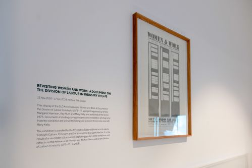 A framed document next to an extract about the exhibition Revisiting Women and Work