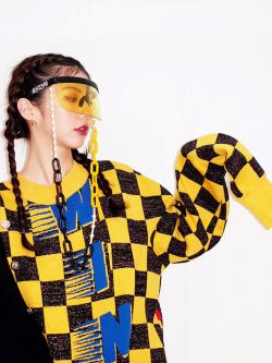 Female model wearing a yellow visor with a yellow and black checked oversize jumper