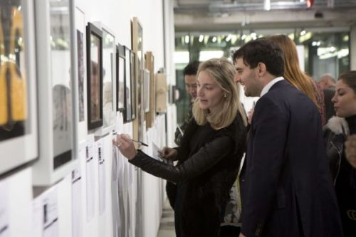 Two people looking at artwork hung on the wall of the gallery, one of them gesturing towards it