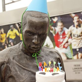 Photograph of a man with a party hat on, holdig a birthday cake and looking angry