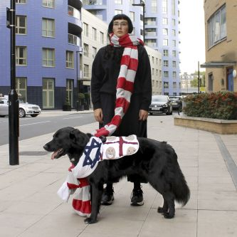 Photograph of a person in a long striped scarf with a black dog stood at their feet