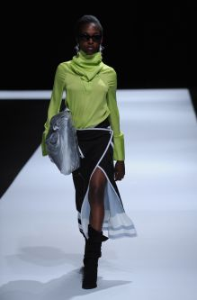 Female model wearing long sleeve neon green top and black and white long skirt designed by Yujin Seo