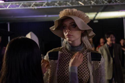 Model wearing a camel bonnet having her outfit altered backstage