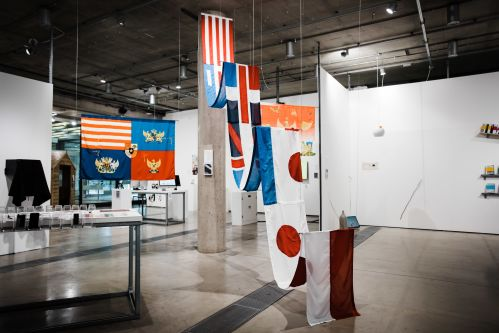 A selection of flags sewn together and hung from the ceiling