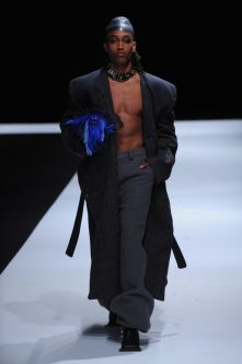 Topless male model with ankle length blazer and hat