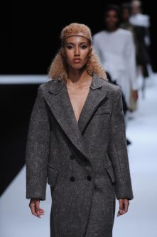 Female model with long, oversized grey woolen blazer.