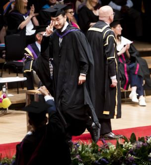 Male graduate walking across the ceremony stage and giving a 'peace' sign to the camera