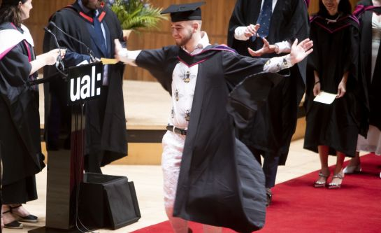 Graduate accepting his award and posing with his arms wide on stage