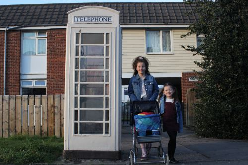 A young adult with a pram and a child standing on a residential street next to a telephone box and smiling.
