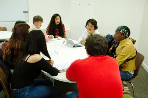 Prospective students sitting round a table talking to LCF staff