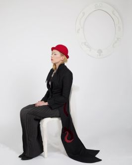 Female model sitting on chair wearing a black suit