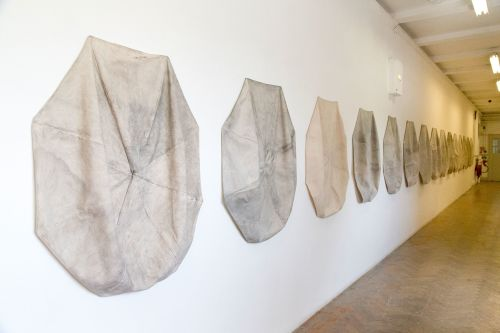 Work by Rebecca Moss. Canvas umbrella tops colured in by pencil and faded by the wind and rain on the coast of England mounted on gallery wall