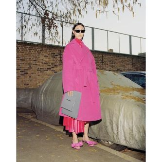 Photograph of a female model in a pink coat and sunglasses standing in a concrete setting