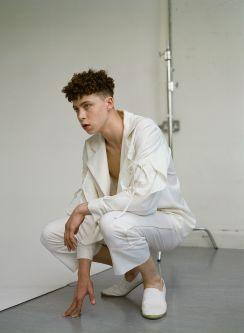 Model crouching in white tailoring