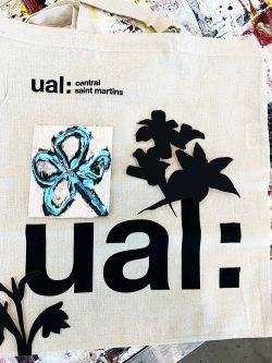 Fabric with UAL logo customized with blue flower painting and additional floral shaped material on top of logo lettering.