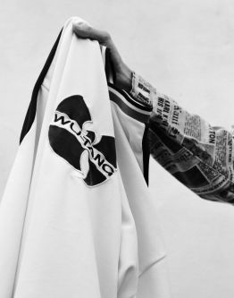 Photograph of a sweatshirt with a Wu-Tang logo being held up
