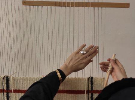 hands weaving on a loom