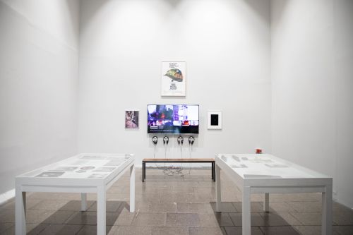 Installation shot of vitrines with work and wall-mounted work with headphones.