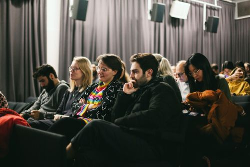 A group of people in lecture seats watching a screening