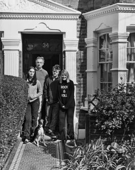 black and white photo of family standing on the doorstep of their home