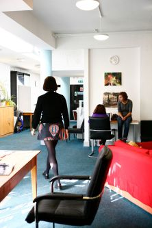Photo of two female students sitting at a computer in a communal area in Cordwainers Court as another student walks past