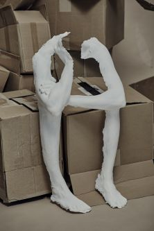 artefact limb cast, crossed arm slumped forward, 'sitting' on a pile of cardboard boxes