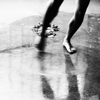 Black and white photo of legs and feet walking in a puddle