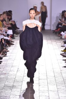 A model walking down a catwalk wearing an navy dress which is oversized around the top half of the body