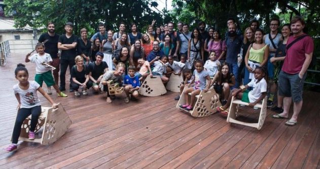A group photo of people stood on  wooden decking with wooden structures